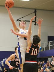 McNary's Lucas Garvey goes up for a shot against McMinnville on Wednesday, Feb. 21, 2018.
