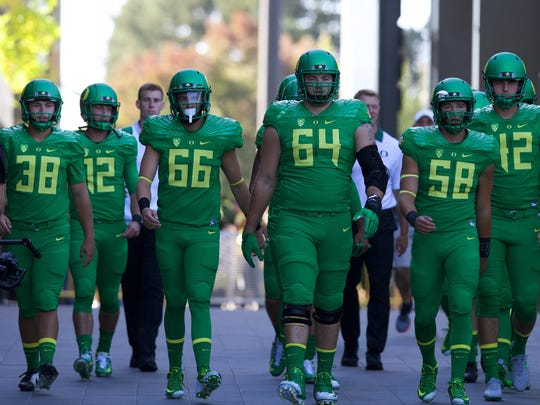 Oregon Ducks long snapper Tanner Carew (58) walks to the field with teammates before a game against the Utah Utes at Autzen Stadium.