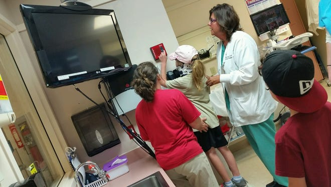 Fera Heckman, 10, tries out equipment at Avera eCare. Heckman was a patient in an eEmergency case in June.