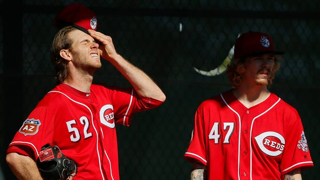 Reds relief pitcher Tony Cingrani (left) wipes his brow of sweat following a bullpen session during spring training in Goodyear, Arizona.