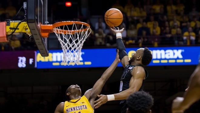 Miami guard Bruce Brown Jr., right, shoots over Minnesota guard Isaiah Washington during the first half at Williams Arena in Minneapolis.