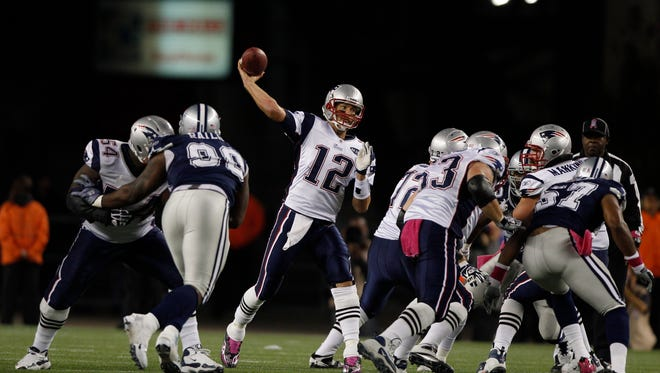 New England Patriots quarterback Tom Brady (12) passes behind the protection of his offensive line during the third quarter of their NFL football game against the New England Patriots in Foxborough, Mass., Sunday afternoon, Oct. 16, 2011.