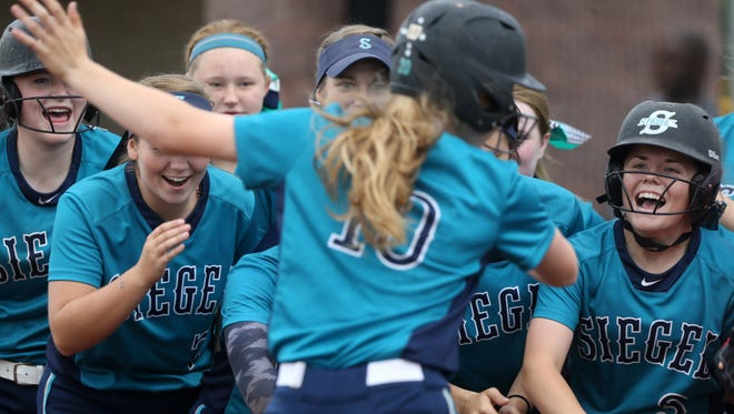 Siegel's Caitlyn McCrary celebrates her solo home run with her teammates during Thursday's District 7-AAA softball championship. Siegel defeated Stewarts Creek 5-0.