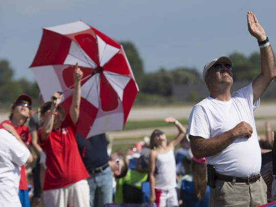 People watch as skydivers jump in an attempt to break a World Record during Wednesday's AirVenture July 22, 2015.
