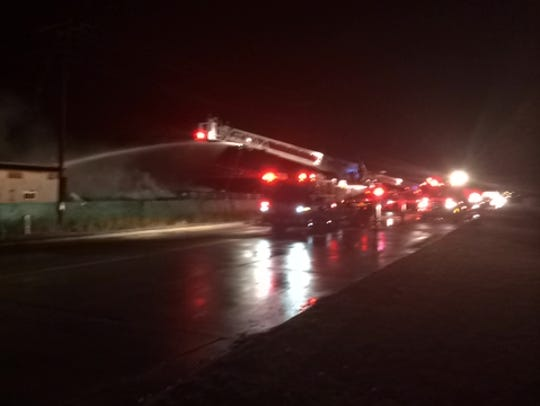 Firefighters use a ladder truck to pour water on the