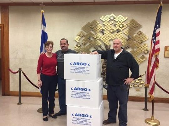 Alexandra Avgitidis, Panagiotis Georgiou of Argos Packing and Shipping and Kostas Apostolakis, custodian at St. George Greek Orthodox Church in Piscataway check out some of the boxes being sent to Syrian refugees in Greece.