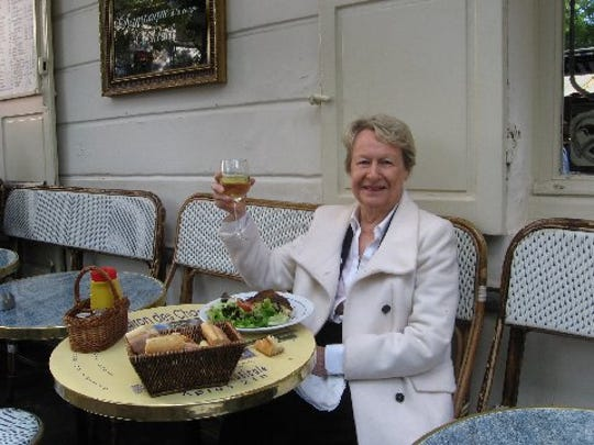 Mary McHugh started writing for the free magazine that came with her diaper service; she has been a magazine writer and editor, and has authors 26 books, including a new Happy Hoofer mystery series. Here she is seated at bistro table, glass of wine in hand.