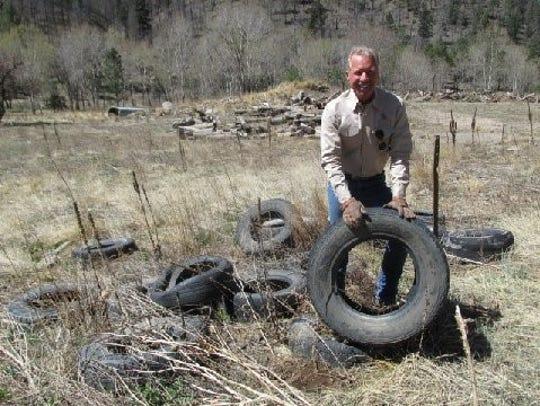 Matthew Midgett picks up abandoned tires to take to