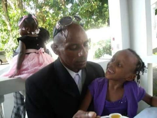 Kenroy Smith with his daughter AbbieGail. Smith is desperately trying to get a visa allowing him to travel from Jamaica to the United States for AbbieGail's funeral.