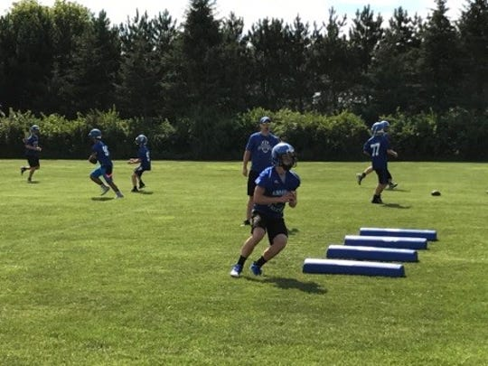 Prospective wide receivers go through a pass-catching drill during the first day of practice for two-time defending Division 5 state champion Amherst on Tuesday.
