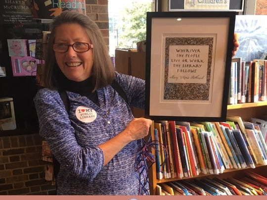 Friends of the Library president Maggie Carini holds
