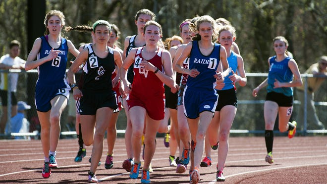 High school girls compete in the 1,500-meter race during the Burlington track and field invitational last month.
