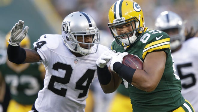 Green Bay Packers tight end Richard Rodgers gains long yardage on a reception against Oakland Raiders safety Charles Woodson.