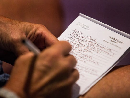 A woman takes notes on flood insurance and claims during