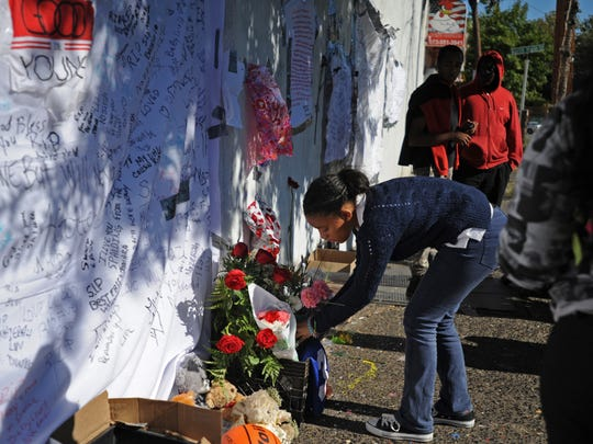 The spot where Nazerah Bugg was shot at North Main and Clinton streets became a memorial after the girl died. Here, Paterson resident Nina Reynoso places a bouquet of flowers in remembrance of the girl.