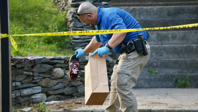 Worcester Police Department crime scene investigator Jeff Fanion places a bloody sneaker into an evidence bag at a crime scene.