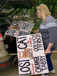 Joan Barch places signs in the area alerting people