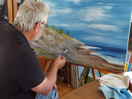 Jim Huff works on a painting of a landscape in his home studio.
