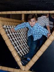 John Thomas Young navigates the new rope bridge at