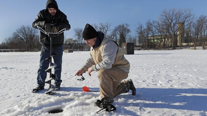Local residents Patric Minehan, left, and Tyler Van Hammond try their luck ice fishing in early January on Little Lake Butte des Morts in Neenah.