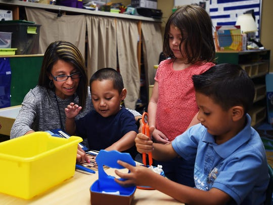 Teacher's assistant Michelle Rivera works with pre-kindergarten students at Booth Elementary School in Reno on Aug. 27. The school now offers all-day pre-K.