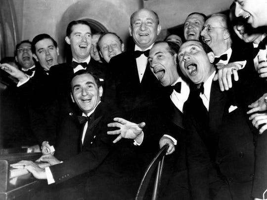 Irving Berlin, at the piano, and friends celebrate his 25th year since he wrote 'Alexander's Rag Time Band' at a banquet in his honor in Hollywood, Ca., Jan. 20, 1936.  Standing behind Berlin, at right, is Joseph Schenck, film producer.  In front row singing together are two of the Marx Brothers, Chico and Harpo.