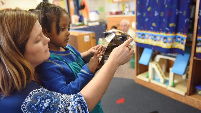 Teacher Tracy Freese reads to student Liya Haile in an early childhood blended classroom at Garfield Elementary on Monday.