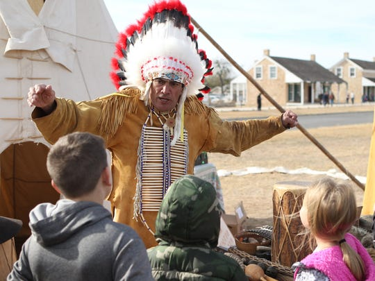 A crowd gathers around the Indian Lore tent as Chief Broken Eagle teaches them about Native American Culture at Christmas at Old Fort Concho.