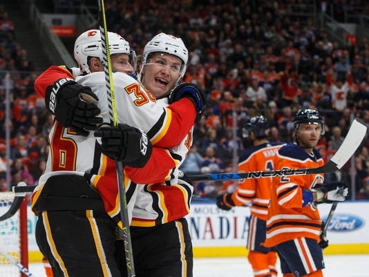 Calgary Flames right wing Troy Brouwer (36) and left wing Matthew Tkachuk (19) celebrate a goal as Edmonton Oilers defenseman Andrej Sekera (2) looks on during first-period NHL hockey game action in Edmonton, Alberta, Thursday, Jan. 25, 2018. (Jason Franson/The Canadian Press via AP)