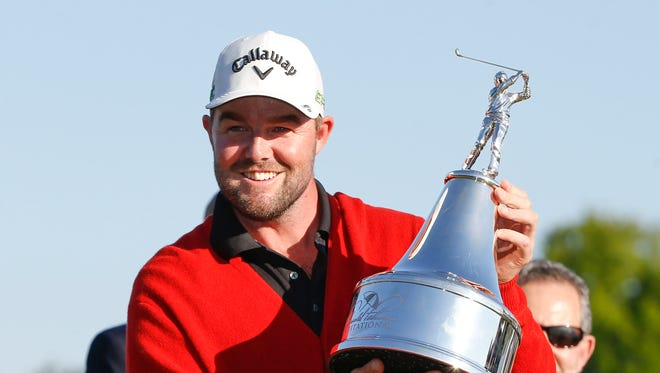 Marc Leishman holds the champions trophy and wears the red memorial sweater after winning the Arnold Palmer Invitational golf tournament at Bay Hill Club & Lodge .