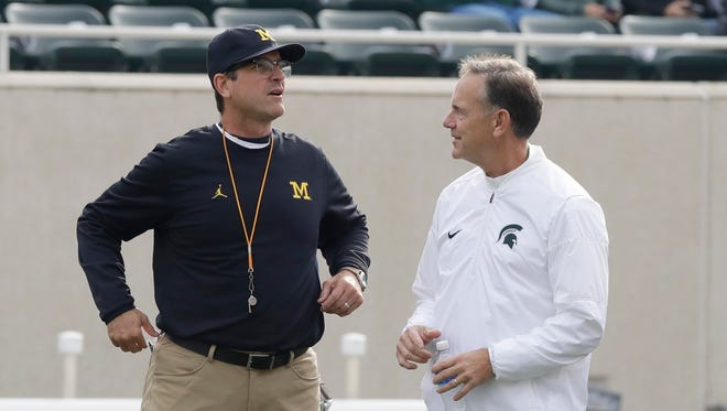 Michigan coach Jim Harbaugh greets Michigan State coach Mark Dantonio before a game in East Lansing on Oct. 29, 2016.