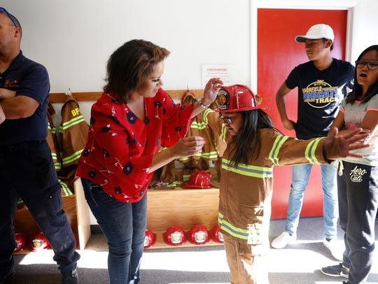 Emily Padilla helps her daughter Mandy Rice put on a costume firefighting suit Thursday during an open house event at the new Bloomfield fire administration building.