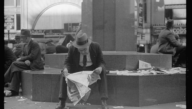 Man reading newspaper in Fountain Square, Cincinnati, Ohio. October 1938.