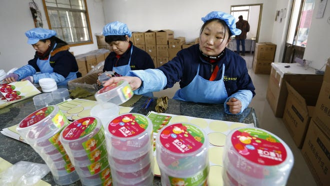 Workers on a pollution mask assembly line in Dongliu, China, on Jan. 27, 2016