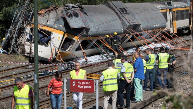 Emergency personnel attend the scene after a passenger train traveling from Vigo to Porto, in neighboring Portugal, derailed in O Porrino,  in Spain's northwestern Galicia region, killing and injuring people, authorities said Sept. 9, 2016.