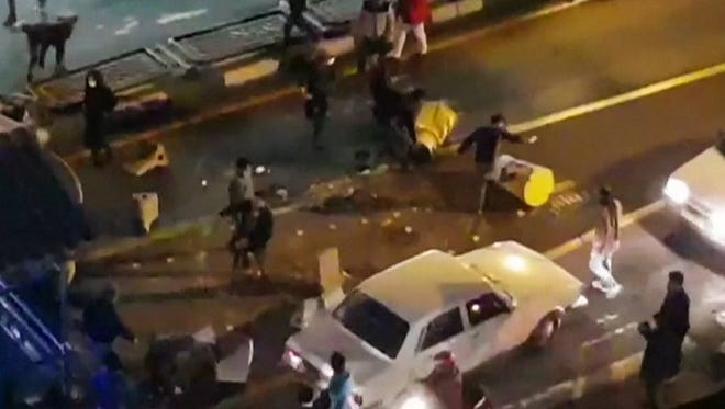 An image grab taken from a handout video released by Iran's Mehr News agency reportedly shows a group of men pushing traffic barriers in a street in Tehran on Dec. 30, 2017.