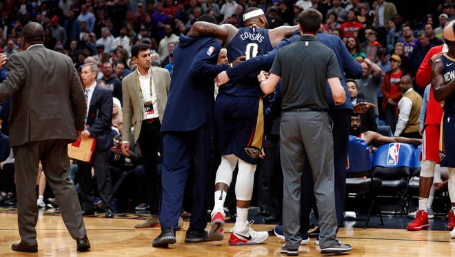 Pelicans center DeMarcus Cousins (0) is helped off the court after injuring his left Achilles' tendon during the fourth quarter against Rockets in New Orleans.