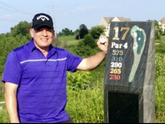 Jeff Hohman stands next to a stone sign marking the distances for the 17th hole at Springwood Golf Course near York. Hohman used a driver to ace the par 4 hole on Saturday from the 310-yard blue tees.