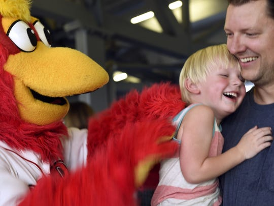 Sounds' mascot Booster has fun with Simon Jones, 3, and his father, Josh, as they enter First Tennessee Park for a game last season.