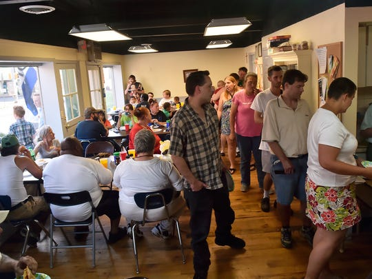 A small packed room of people eat food or wait in line inside Queen Street Mission for a free meal on Friday, June 17, 2016, in Chambersburg, Pa. Queen Street Mission serves free meals twice a week to about 50 people.