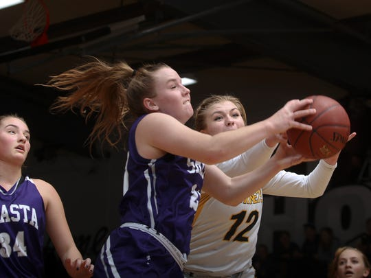 Shasta High's Cate Walton, center, and Enterprise's Meagan Briggs, right, go for a rebound Friday night.