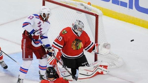 Rangers prospect Anthony Duclair, left, and Chicago Blackhawks goalie Corey Crawford watch the puck go past the net during a preseason game Friday night.