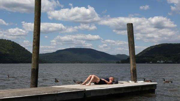 A sunbather  on a dock along the Hudson River in Peekskill.