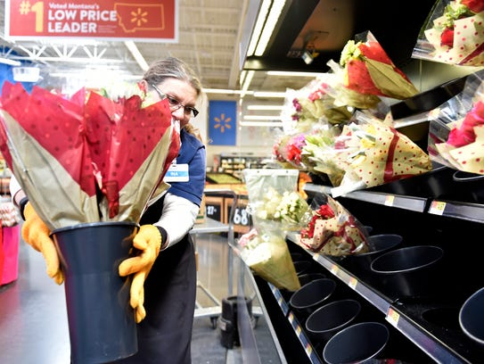 Ina Onsager, a Wal-Mart produce sales associate, restocks flowers at the 10th Avenue South Wal-Mart on Wednesday afternoon.