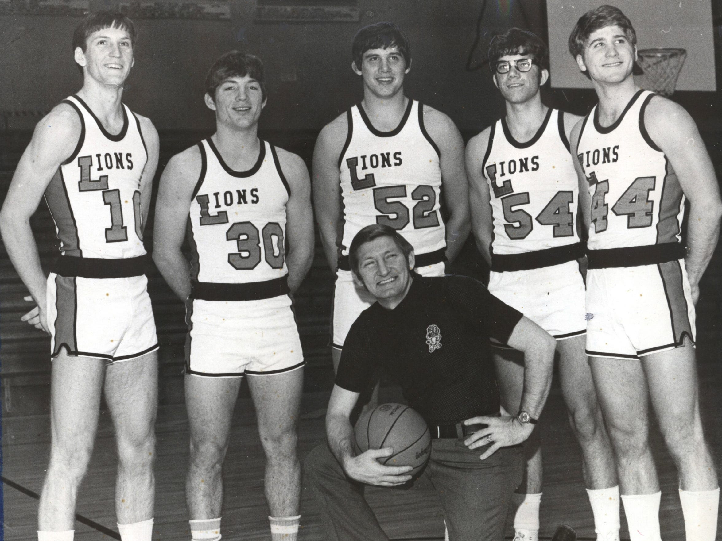 The 1975 Loogootee Lions huddle around coach, Jack Butcher. From left are Bill Butcher, Kenny Mattingly, Mike Walls, Kenny Nigg and Mark Riggins.