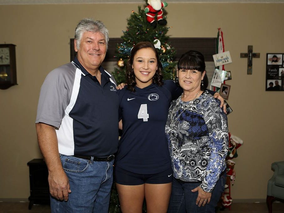 Penn State senior volleyball player Dominique Gonzalez stands in front of the family Christmas tree with her father, Roger, and mother, Debra.