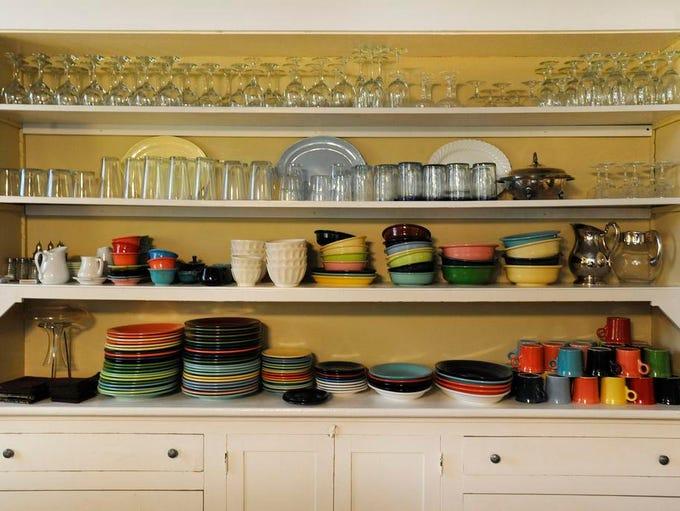 A cabinet full of dinnerware, including original Fiestaware,