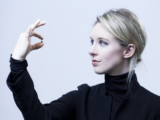 Theranos founder Elizabeth Holmes holds one of her