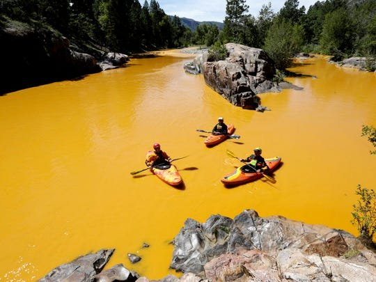 People kayak in the Animas River near Durango, Colo.,