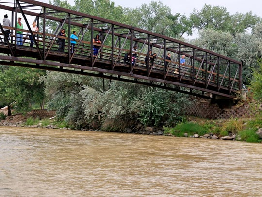 Onlookers view the Animas River from a bridge as orange